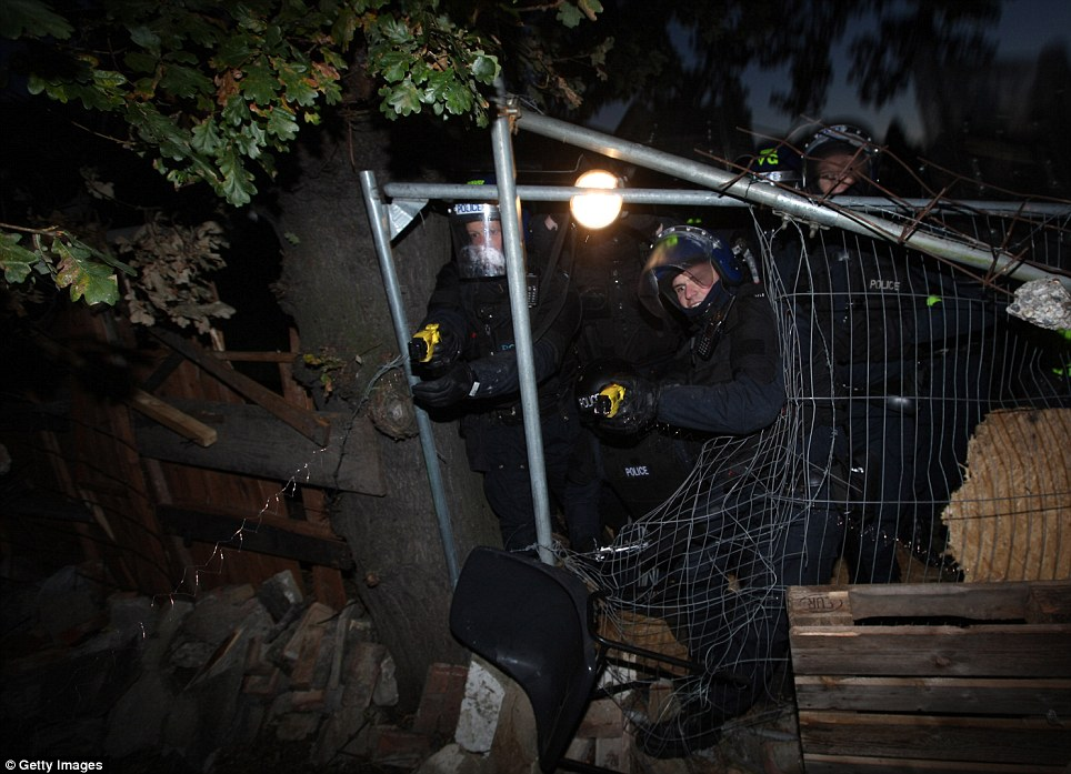 Shock tactics: Police fire Tasers as they force their way past a metal barricade in the perimeter of the compound