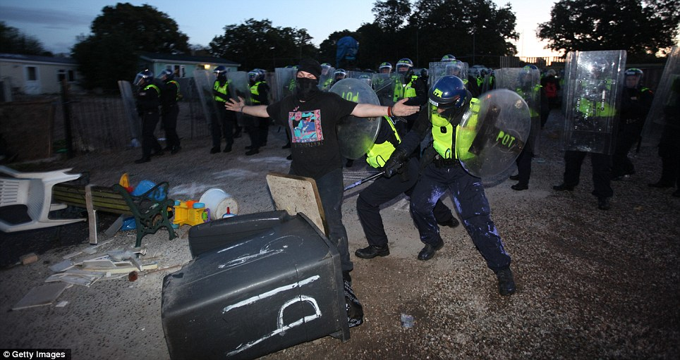 Long arm of the law: An anarchist is hit in the leg by a baton as police show little leniency while entering the site