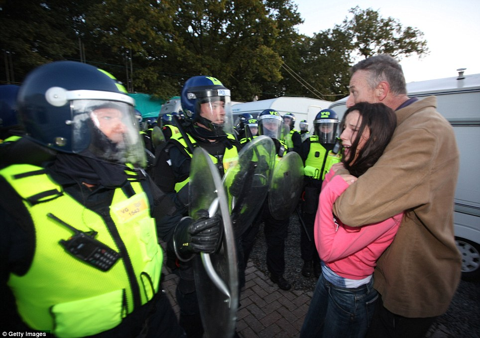 Move over: An emotional traveller girl is embraced by a relative in front of police as evictions begin