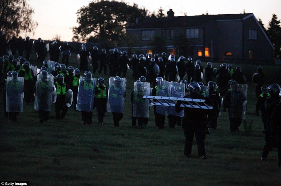 Coming over the hill: An army of riot police march towards the site this morning as the battle of Dale Farm began