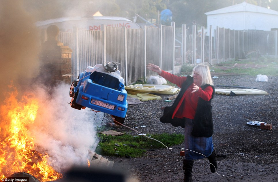 Adding fuel to the fire: Traveller Kathleen McCarthy tosses a toy car onto a burning caravan as she realises that the tide is turning against them