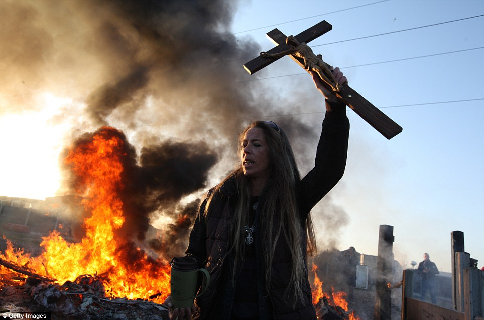 Last stand: An activist holds aloft a crucifix in one hand and a mug of tea in the other as behind her a caravan is burned to the ground