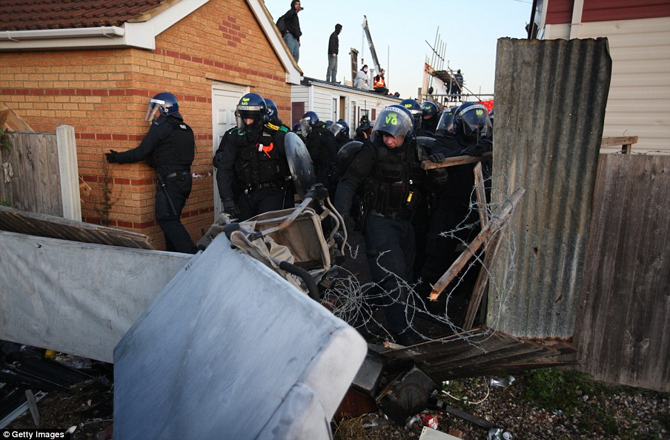 Destruction: Police push through hazards and booby traps such as barbed wire and corrugated iron. One officer appears to be checking around the corner of a home to ensure no anarchists are lying in wait