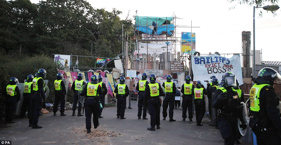 Stalemate: Police stand outside the main entrance as they begin phase two of the demolition. They are unable to knock through the scaffolding in case protesters are injured