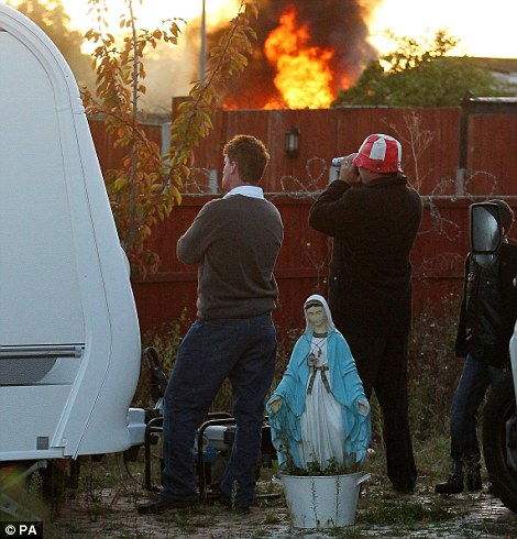 Residents at the legal travellers site watch as smoke and flames rise from Dale Farm