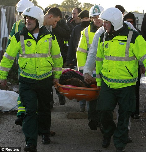 Paramedics carry away on a stretcher Nora Egan, who fell over injured her back during the clashes