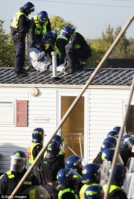 Police strap together the legs of an anarchist in a white boiler suit who was lying on the roof of a building