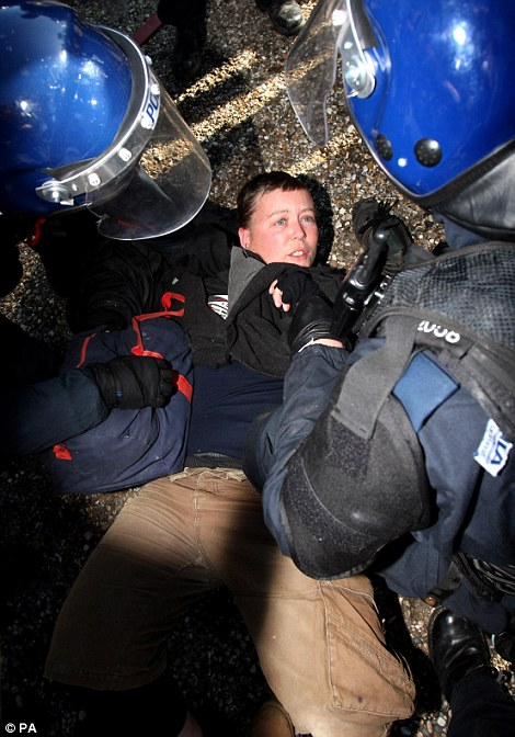 A protester is picked up from the floor to be removed from the site