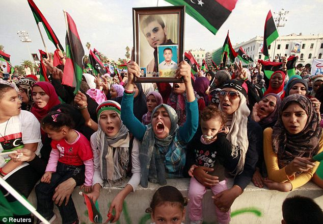 Tripoli: A woman holds up a photo of a relative during post-liberation celebrations at Martyrs' Square
