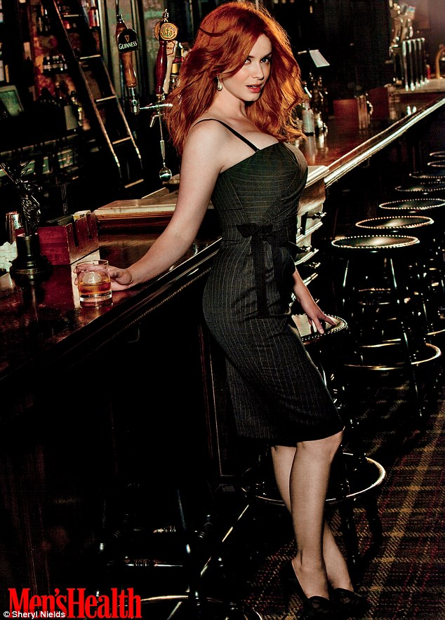 Last orders: Christina Hendricks poses in a grey pinstripe dress with a glass of whiskey at a bar in the new issue of Men's Health magazine