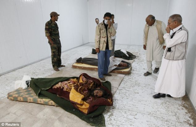 Stench: Libyan people cover their faces as they visit the body of their slain former leader inside a storage freezer in Misrata