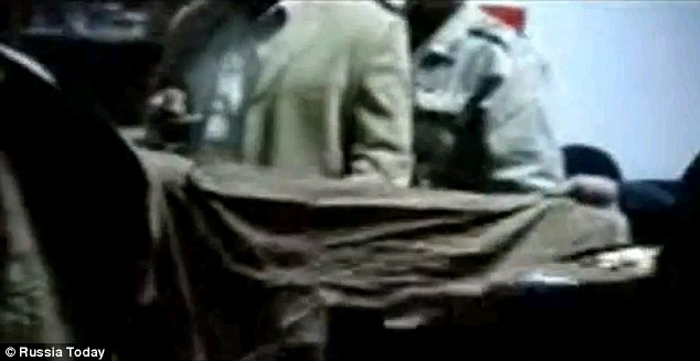 The evidence: Men hold up a bloodstained smock, purportedly the one Colonel Gaddafi was wearing when he was discovered, beaten and shot dead