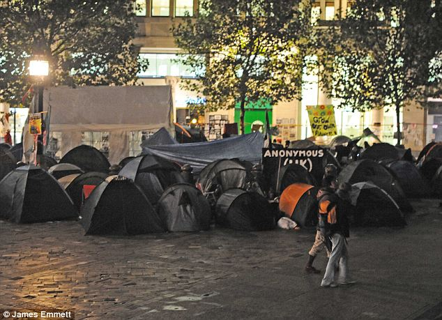 Tent city: A couple walk by the damp protest shanty town last night, lit by the glare of the street lights