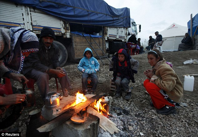 Survival: People huddle round a fire in Guvecli, 20 miles from the town of Van, after the quake destroyed their home