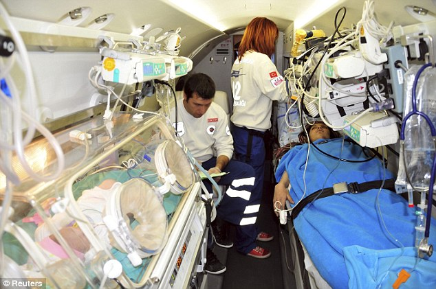 Care: The little girl and her mother Semiha are treated by medics in an ambulance plane as they were flown to a hospital in Ankara