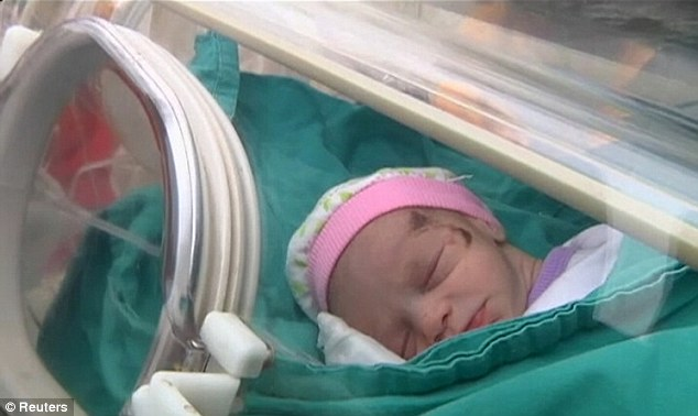 Safe: Little Azra sleeps in an incubator after arriving at the hospital in the Turkish capital
