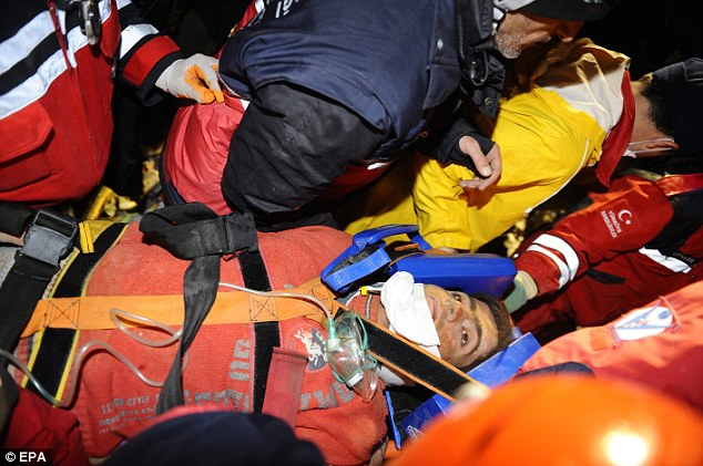 Another survivor: Imdat Padak is carried into a waiting ambulance