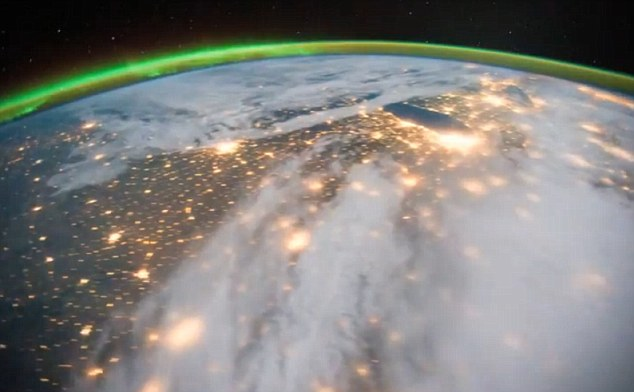 The northern lights shimmer over the horizon as the International Space Station passes over the brightly lit cities of America beneath