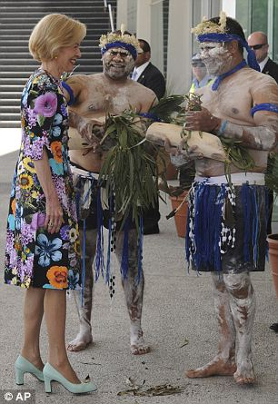 Australia's Governor General Quentin Bryce is greeted by aborigines who purify her with smoke from burning grass