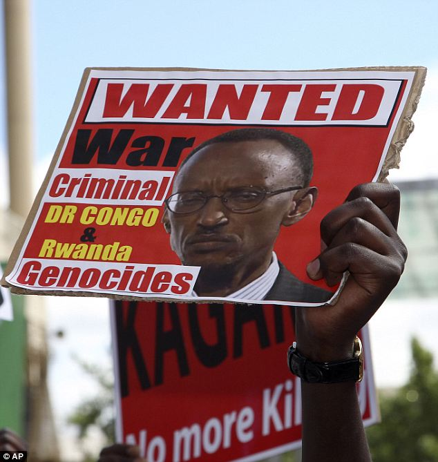 A man holds up a protest sign with the face of Paul Kagame, the Rwandan president, that reads, 'Wanted war criminal: DR Congo & Rwanda genocides'