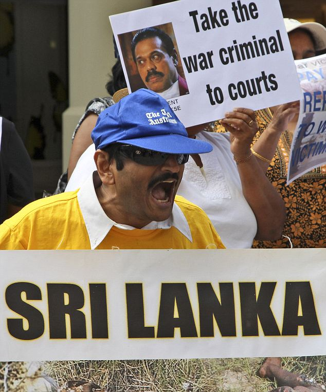 Sri Lankan protesters outside the Commonwealth summit hold pictures of human rights abuses in the country and placards with the face of Sri Lankan president Mahinda Rajapaska which read: 'Take the war criminal to courts'
