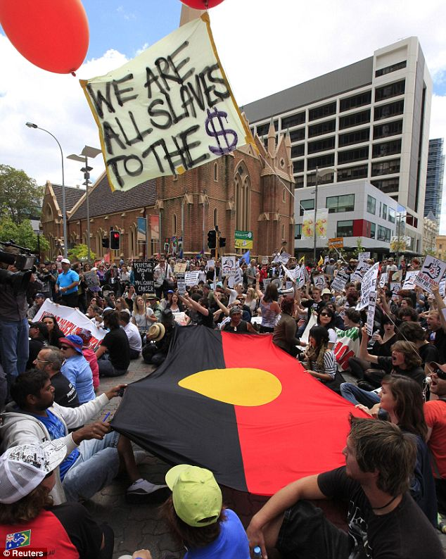 Protesters surround an Australian Aboriginal flag in front of Wesley Church near the venue of the Commonwealth Heads of Government Meeting as a banner reading, 'We are all slaves to the $' is held aloft by helium balloons