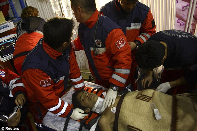 Treated: A visibly shaken Serhat Tokay was dragged from the rubble after 100 hours