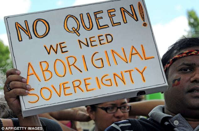 An Aborigine protester holds a placard which reads, 'No Queen! We need Aboriginal sovereignty', as the Queen opened the biennal Commonwealth heads of government meeting