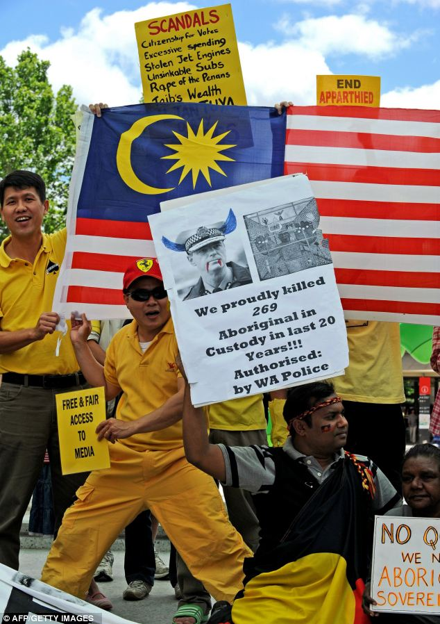 Malaysian and Aborigine protesters hold banners and placards against alleged human rights abuses committed by regimes represented at the Commonwealth summit