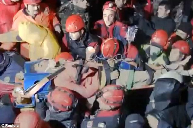 Rescue: Serhat Tokay, 13, was put in a neck brace and taken by workers on a stretcher to a waiting ambulance