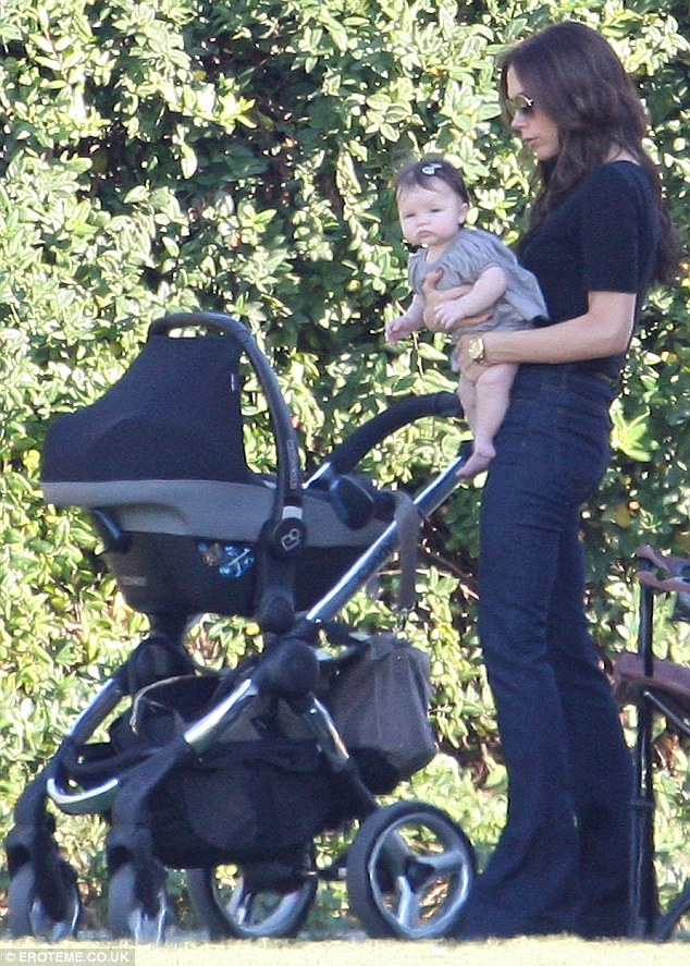 Out of the sun: Victoria Beckham hept baby Harper in the shade while they watched the boys play football in Los Angeles yesterday