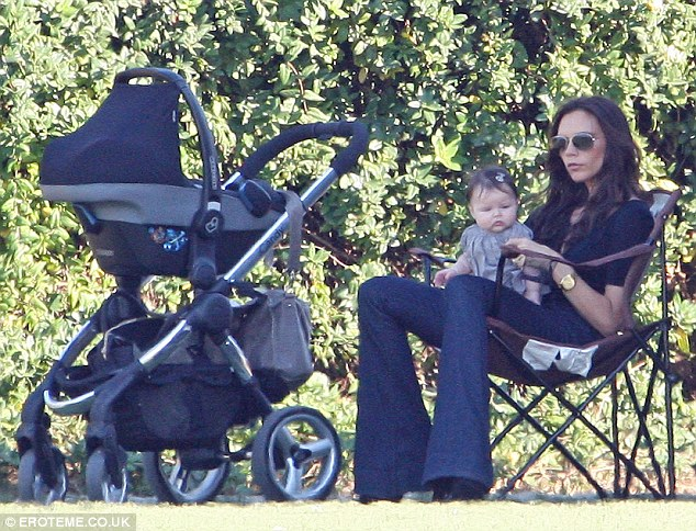 No running about for us: The pair sat down in the shade, a perky Harper sitting up on Victoria's lap