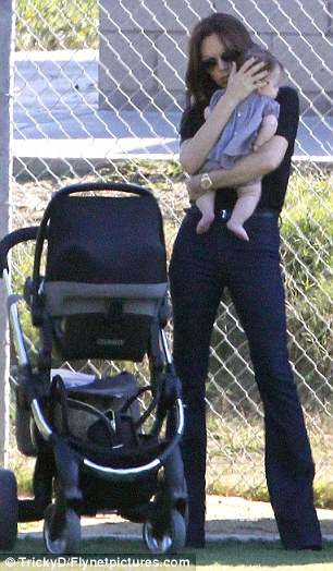 Cuddles: Victoria just can't get enough of her baby girl as she snuggled her close