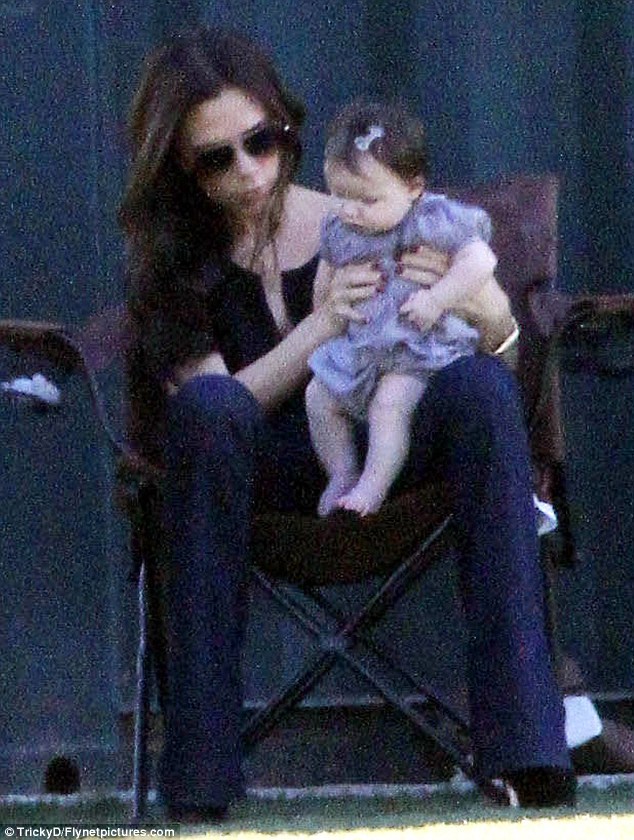 Bouncy baby: Victoria holds a fidgety Harper on her lap as she spots something on the ground