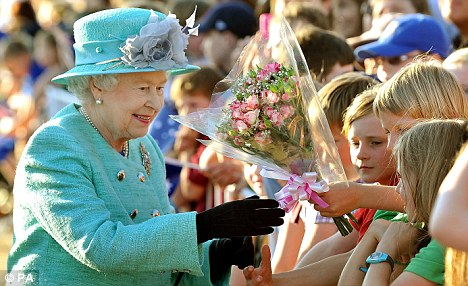 Warm welcome: The Queen is given flowers by school children during a short walkabout
