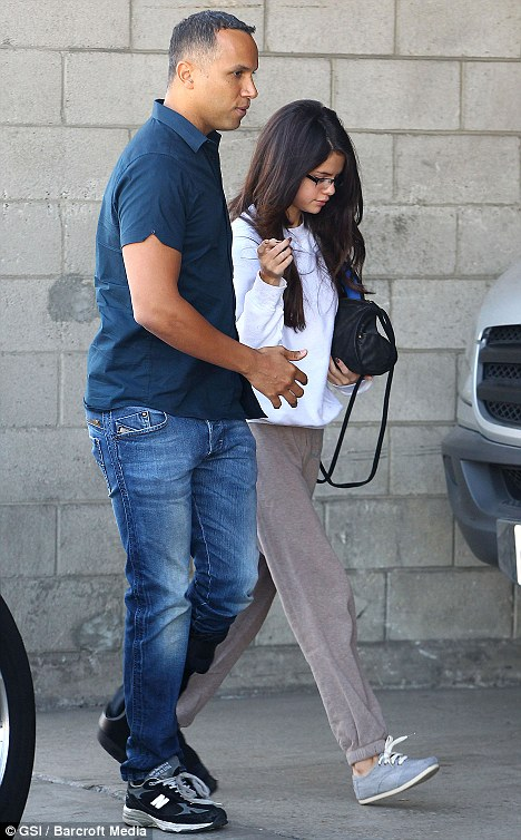 Dressed down: Selena is seen being escorted to work at an L.A studio by a bodyguard this morning as the story hits fever pitch
