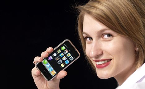 A young woman holding an Apple iPhone mobile phone.