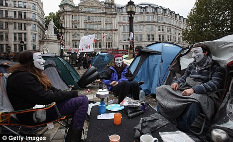 Protest camp: Masked demonstrators outside St Paul's Cathedral which has been daubed and human waste left inside the building