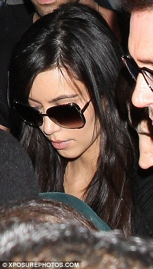 Glum: Kim, seen right arrive back from Australia, and Kris pictured last week