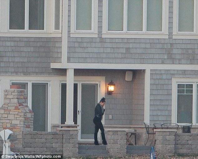Solitary figure: Kim can be spotted pacing the porch in sombre black
