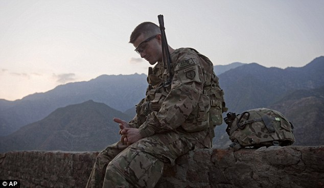 Alone with his thoughts: Andrew has a moment of reflection in the cool dusk air of the Kunar province at  Observation Post Coleman