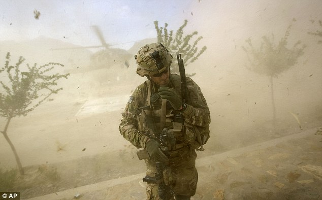Dust is the enemy: Andrew turns from the rotor wash of landing Blackhawk helicopter during a mission in Shigal