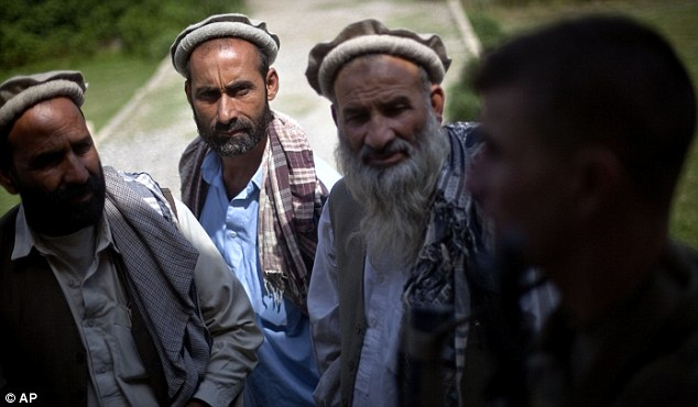 Troubling times: Andrew talks to local men. Soldiers have had to come to terms with befriending locals while fighting insurgents