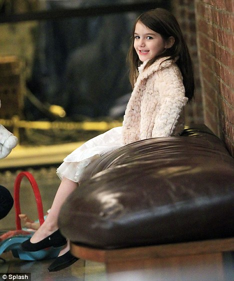 This is comfortable: Suri relaxed on a brown leather sofa in the hotel lobby