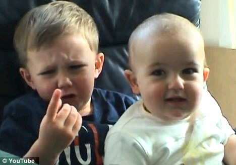 Hit: Harry Davies-Carr, three, looks at his sore finger which was bitten by his cheeky one-year-old brother Charlie. The video has become an internet sensation