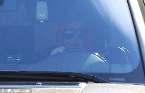 Driving visit: Kim was spotted looking low key today with a red hat and oversize sunglasses as she is reported to have visited music manager Irving Azoff