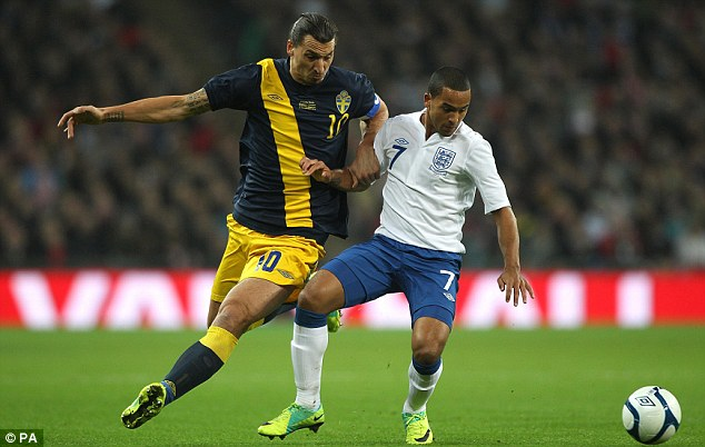 Fend off: England's Theo Walcott (right) holds off Sweden's Zlatan Ibrahimovic