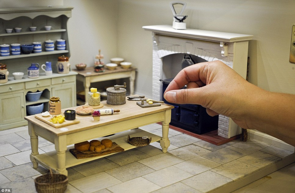 Hands reach in for a miniature butter-pat in a kitchen scene at the shop