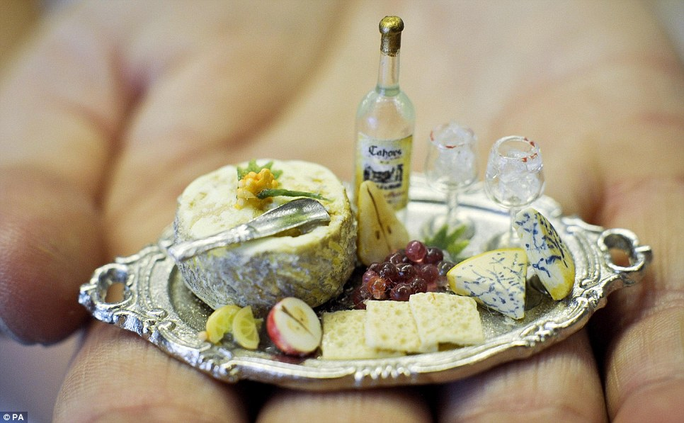 A platter of cheese and biscuits with fruit, wine, silver cheese scoop and wine glasses, made with real glass