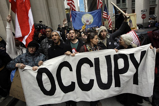 On the move: Demonstrators affiliated with the Occupy Wall Street movement march through the streets of the financial district on Thursday in New York